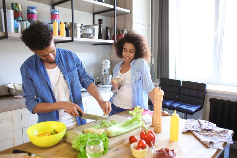 Young African-American woman drinking wine and her boyfriend cooking in kitchen. Young African-American women drinking wine and her boyfriend cooking in kitchen stock photos