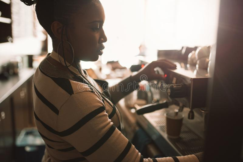 Young African barista pouring coffee behind a cafe counter. Young African barista pouring fresh coffee into a takeaway cup while working behind the counter of royalty free stock photo