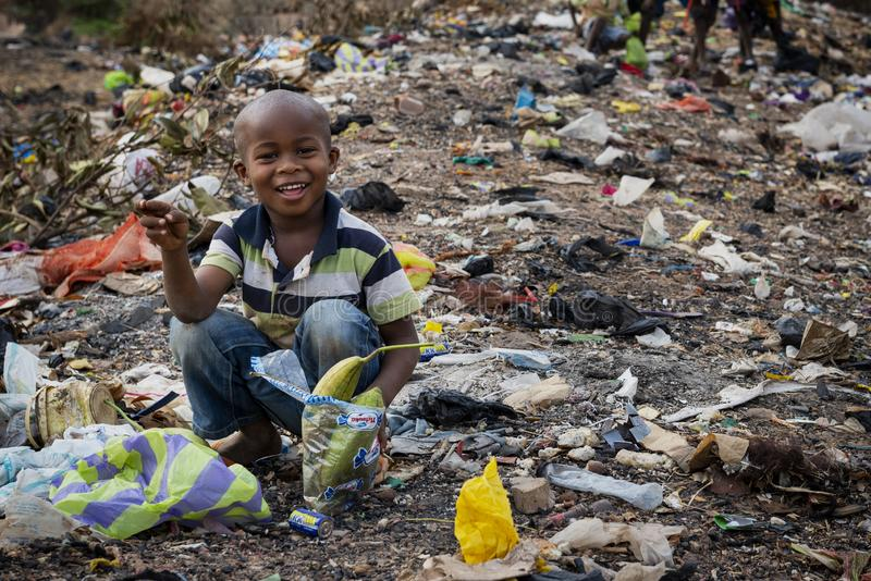 Young african boy collecting garbage at a landfill in the city of Bissau, in Guinea-Bissau. Bissau, Republic of Guinea-Bissau - February 8, 2018: Young african royalty free stock image