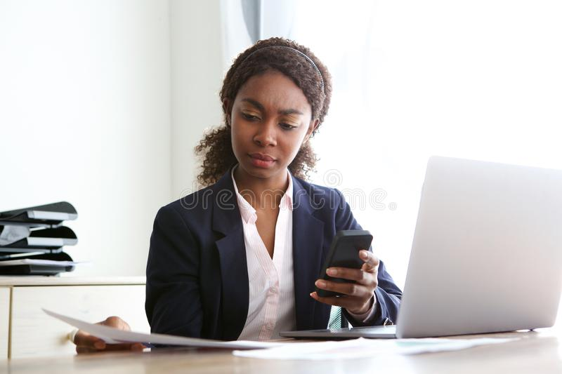 Young african business woman sitting at her desk and reviewing documents. Portrait of young african business woman sitting at her desk and reviewing documents royalty free stock photography