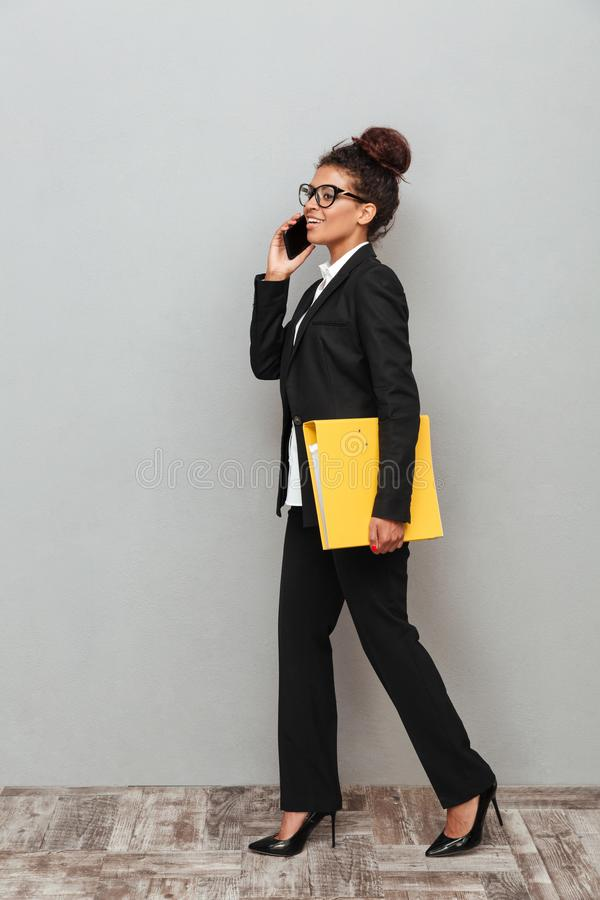 Young african business woman standing over grey wall. Image of young african business woman standing over grey wall looking aside talking by phone holding stock images