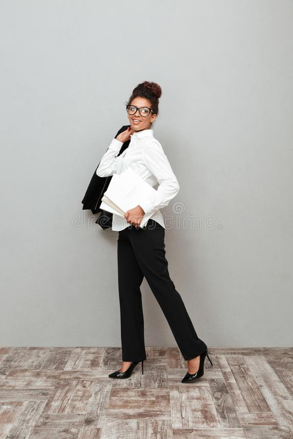 Young african business woman standing over grey wall. Image of young african business woman standing over grey wall looking aside holding documents stock photography