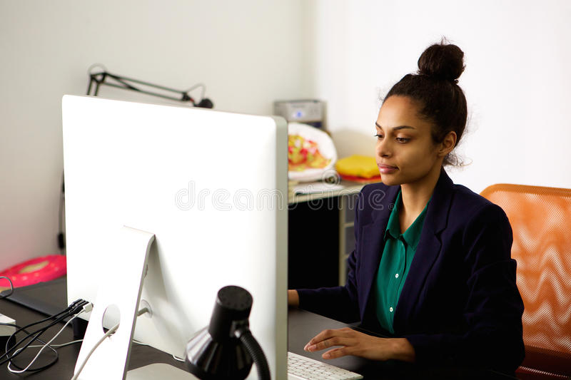 Young african business woman working at her desk. Portrait of young african business woman sitting at her desk using desktop computer at office royalty free stock photos