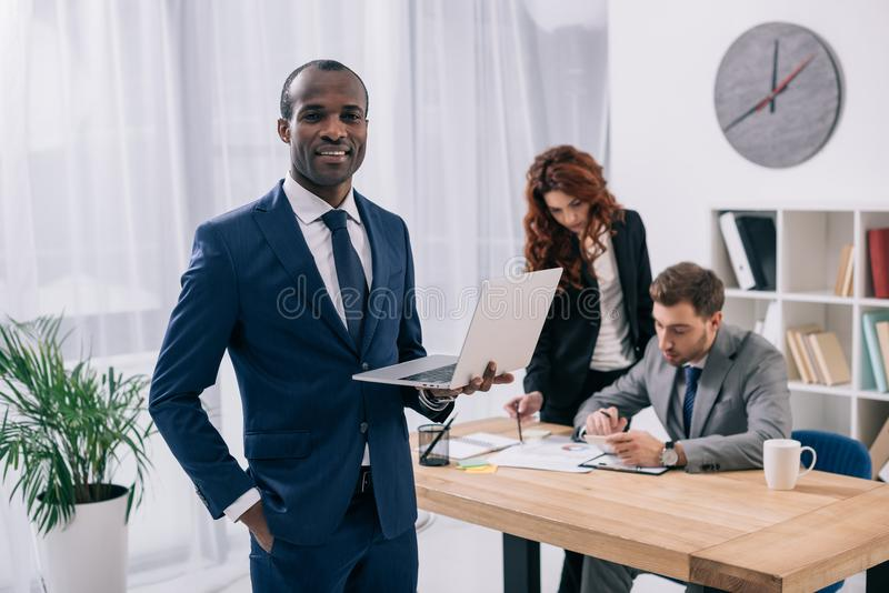 Young african businessman with laptop and two colleagues doing paperwork royalty free stock photos