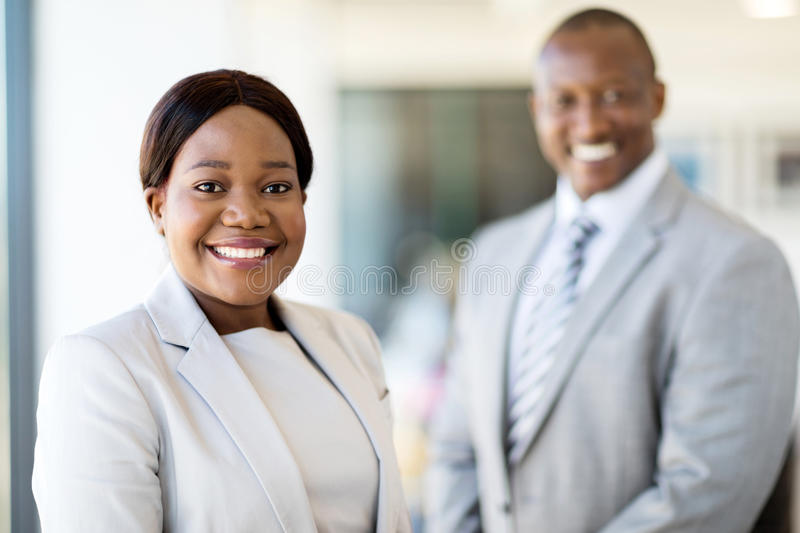 Young african businesswoman. Beautiful young african businesswoman standing in front of her colleague royalty free stock images