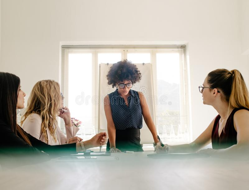 Group of women having a meeting in boardroom. Young african businesswoman sharing her ideas to female colleagues sitting around conference table in modern office royalty free stock images