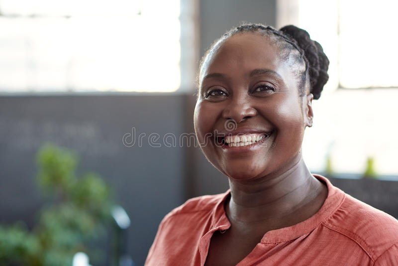 Young African businesswoman smiling confidently in an office royalty free stock images