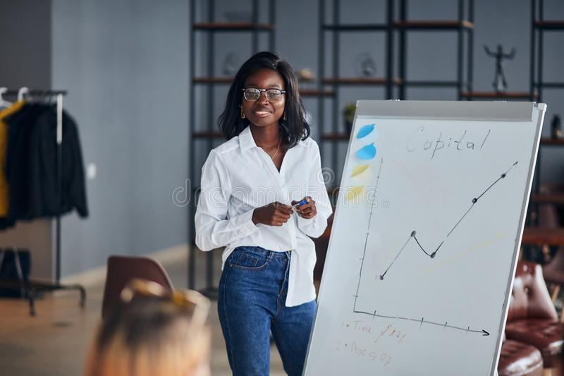 Young african businesswoman stand talking explaining making flip chart presentation stock photos