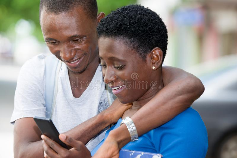 Close up of young african couple, happy. Young african couple sitting looking at mobile phone while laughing stock images