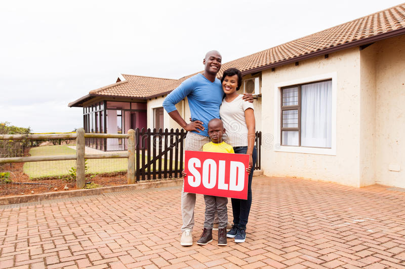 Young african family home. Happy young african family in front of their home with sold real estate sign royalty free stock image