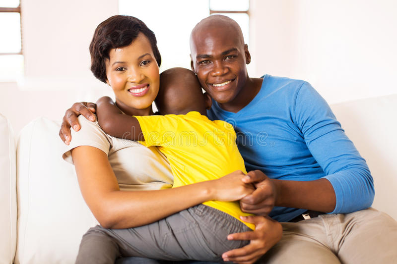 Young african family home. Lovely young african family of three sitting at home stock images