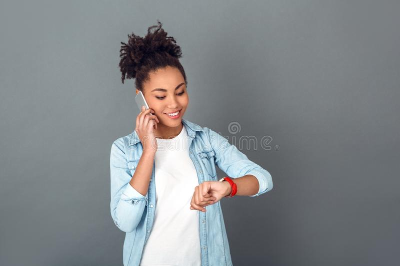 Young african woman on grey wall studio casual daily lifestyle looking at watch. Young african female student on grey wall having phone call talking with friend stock photos