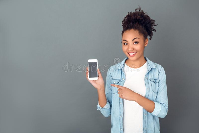 Young african woman on grey wall studio casual daily lifestyle holding smartphone. Young african female student on grey wall holding smartphone pointing at it stock images