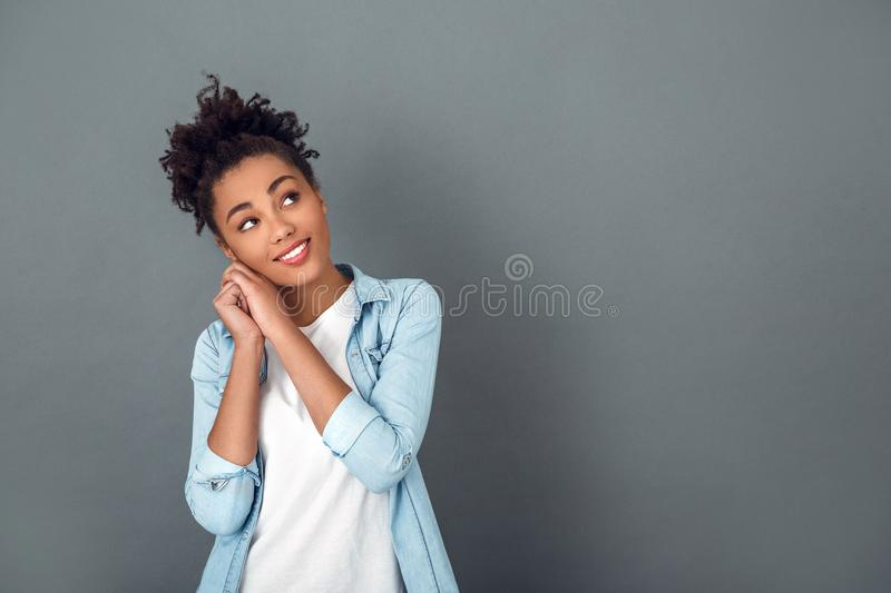 Young african woman isolated on grey wall studio casual daily lifestyle dreaming. Young african female student isolated on grey wall looking up dreaming about royalty free stock photography