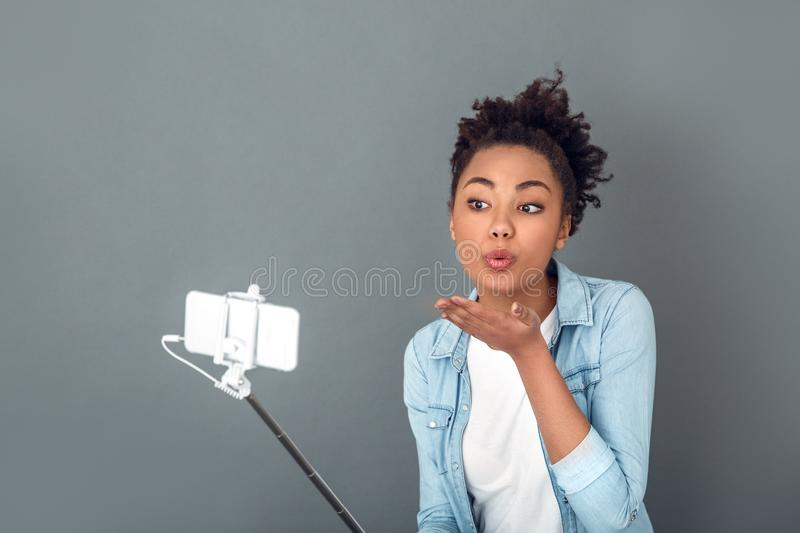 Young african woman isolated on grey wall studio casual daily lifestyle air-kiss. Young african female student isolated on grey wall taking selfie pictures royalty free stock images