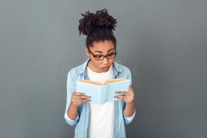 Young african woman isolated on grey wall studio casual daily lifestyle student reading book confused. Young african female student isolated on grey wall wearing royalty free stock photography