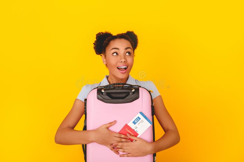 Young african woman isolated on yellow wall studio cute style traveler concept holding baggage dreaming royalty free stock photo