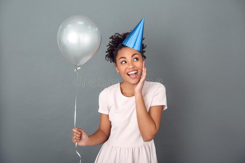Young african woman isolated on grey wall studio celebration concept holding balloon cheerful stock photo