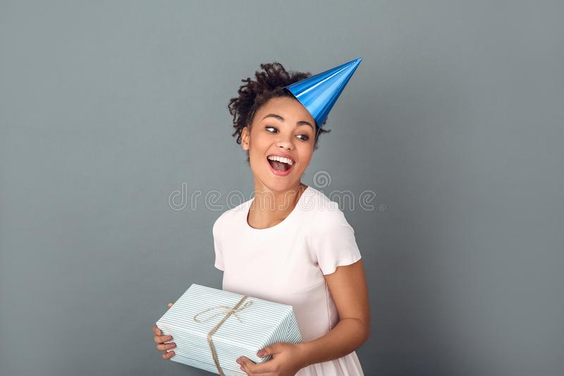 Young african woman isolated on grey wall studio celebration concept hugging present royalty free stock photos