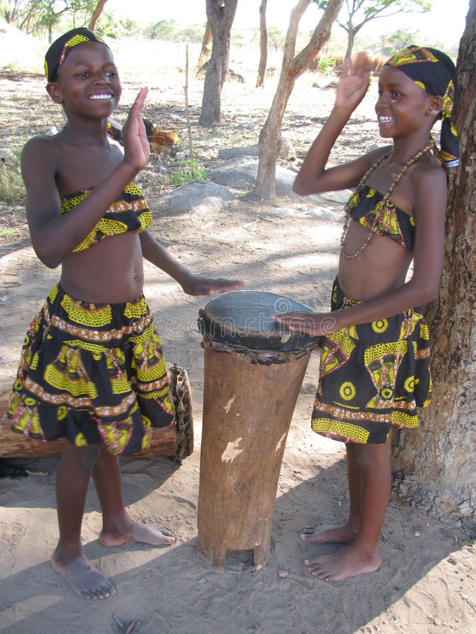 Young African girls in cultural attire playing drums royalty free stock photo