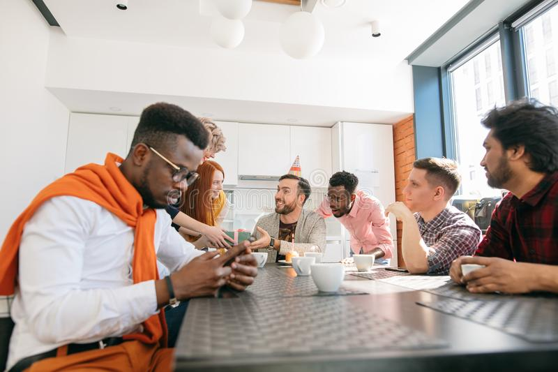 Young african guy with mobile phone ignoring his co-workers birthday. Introvert in the collective stock photo