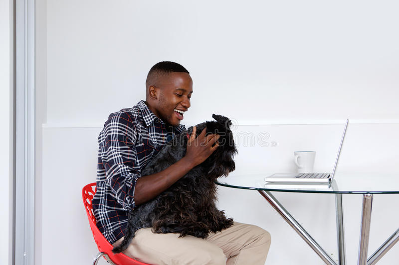 Young african guy playing with his pet dog. Side portrait of young african guy sitting at a table playing with his pet dog at home while working on laptop royalty free stock image