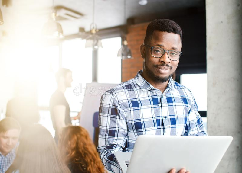 Young African guy is testing laptop stock photography