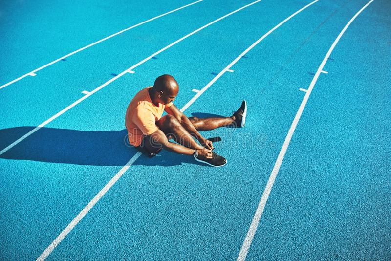 Young athlete tying up his shoes before a run. Young African male athlete in sportswear sitting alone on the lanes of a running track tying up his running shoes royalty free stock image