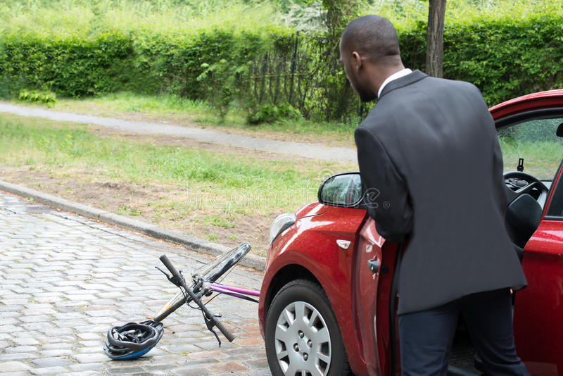 Young African Male Driver Looking At Bicycle. Rear View Of A Young African Male Driver Looking At Bicycle After Collision On Street royalty free stock photography