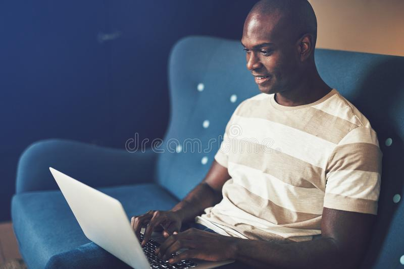 Smiling African entrepreneur sitting on a couch working online royalty free stock photo