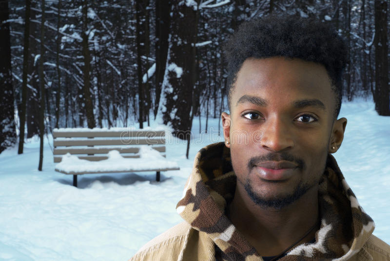 Young african male in snow winter park outside royalty free stock image