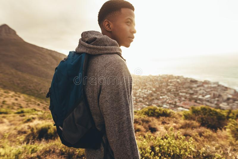 Young guy on hiking trip. Young african man with backpack standing on hill and looking at a view with bright sunlight from back. Young guy on hiking trip stock photos