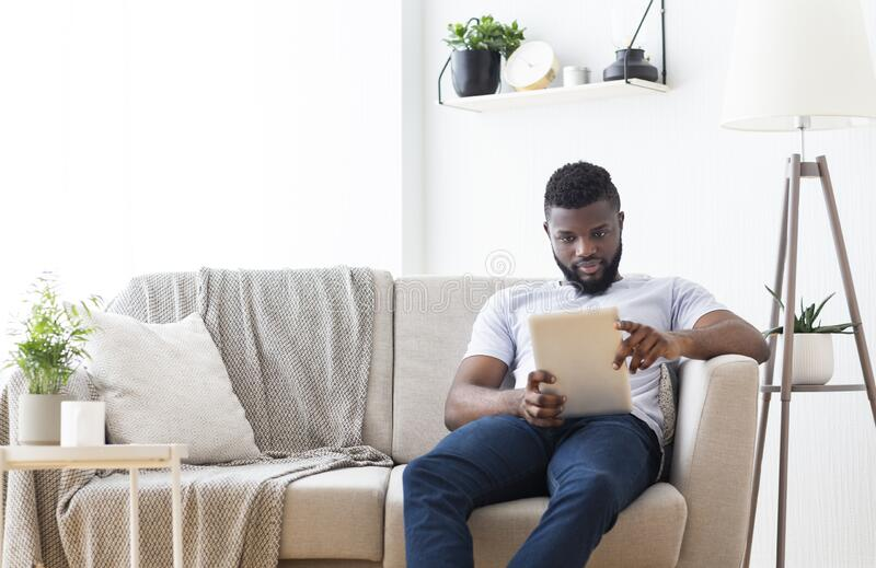Young african man browsing on digital tablet at home royalty free stock images