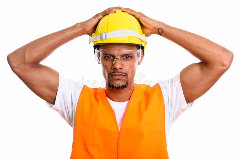 Young African man construction worker with both hands on safety. Helmet stock photos