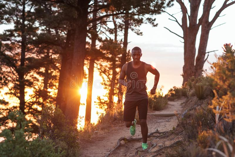 Young African man cross country running along trail at dusk stock image