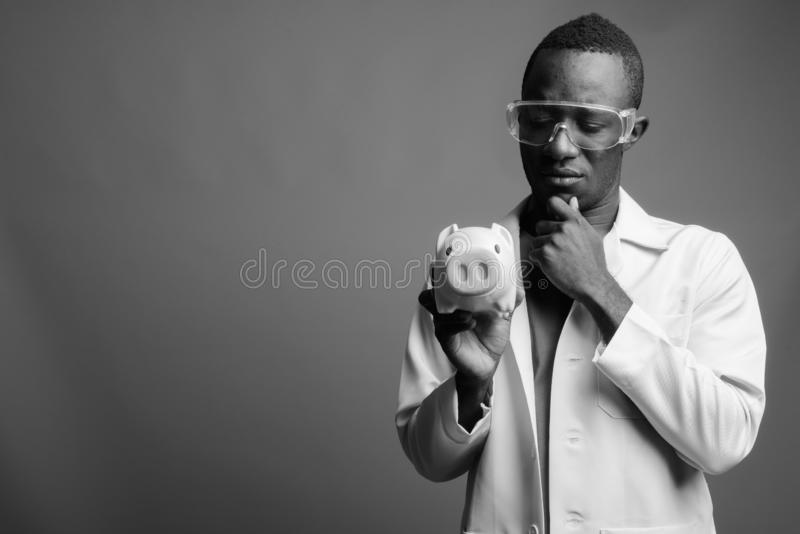 Young African man doctor as scientist with protective glasses in black and white royalty free stock image