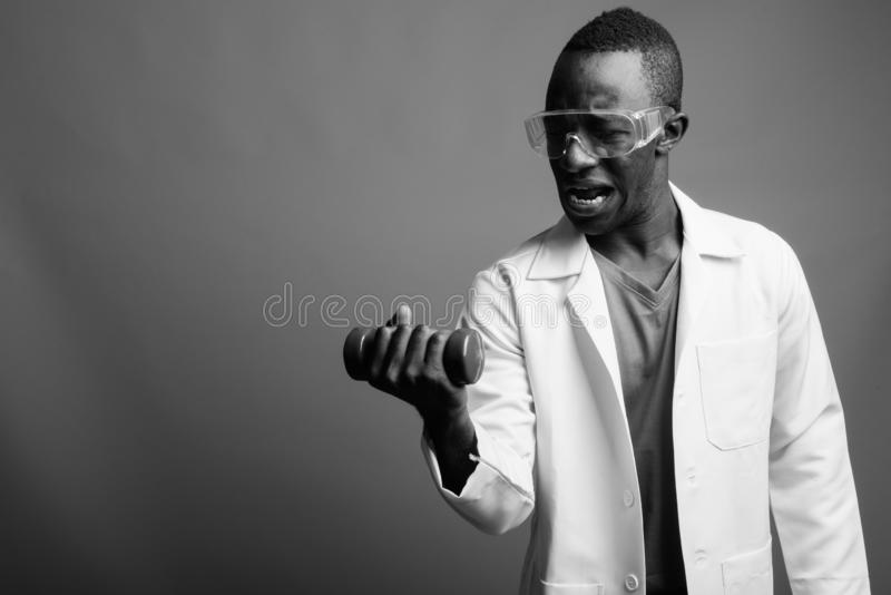 Young African man doctor as scientist with protective glasses in black and white royalty free stock photos