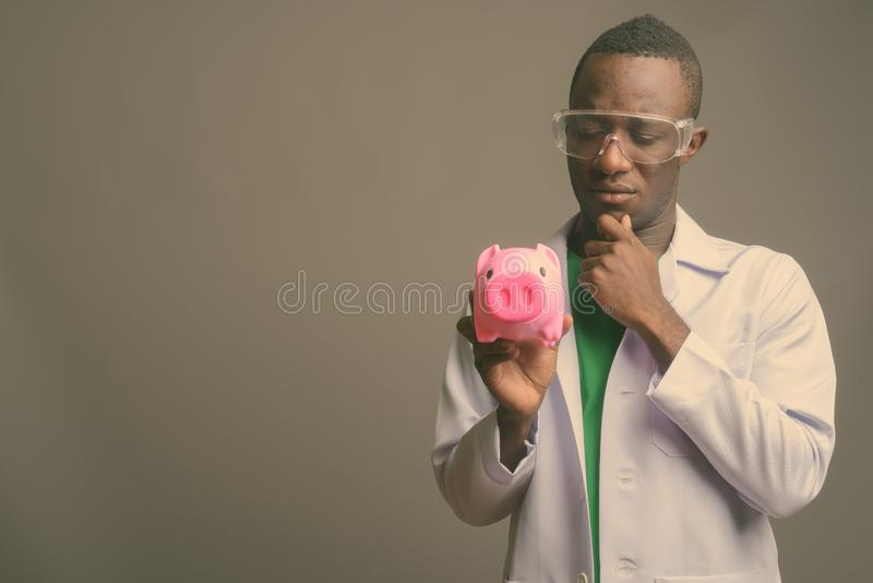 Young African man doctor wearing protective glasses against gray background stock photos