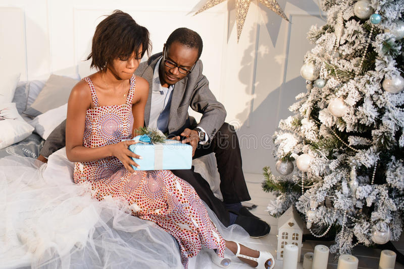The young african man is giving a present box to his beautiful girlfriend on the Christmas Eve stock photo