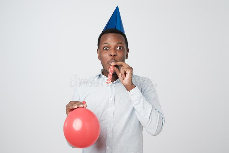 Young african man having fun on party wearing blue shirt and holiday hat, blowing party horn. royalty free stock image