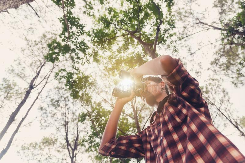 Young African man looking through binocular in the forest, Travel concept. royalty free stock photography