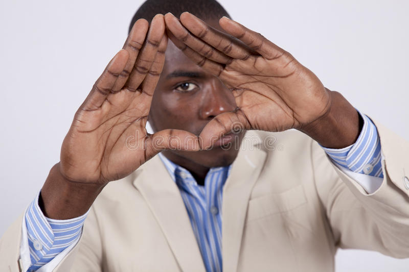 Young African man looking through his hands stock photo