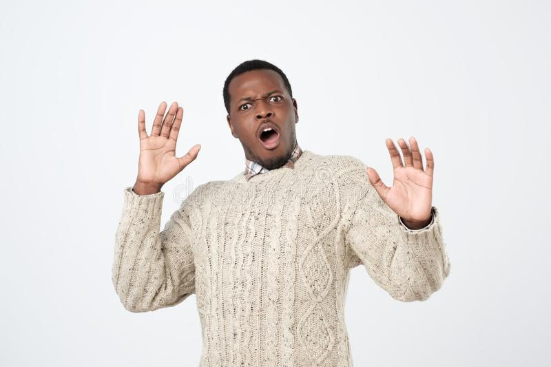 African man looking scared as noticing ghost tilting backwards and raising hands in surrender being terrified. Young african man looking scared as noticing ghost stock photos
