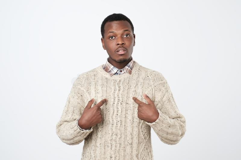 Young african man pointing at himself, making excuses or verbally defending, having perplexed and puzzled. Human face expressions stock image