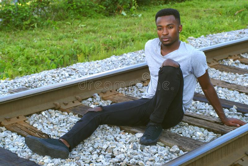 Young man sitting on railroad track african twenties outdoor portrait royalty free stock photo
