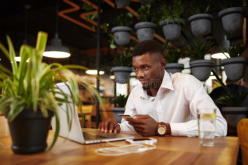 African man shoping at internet shop with card and laptop. royalty free stock photography