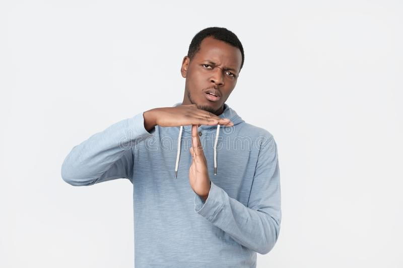 Young african man showing time out hands gesture . stock image