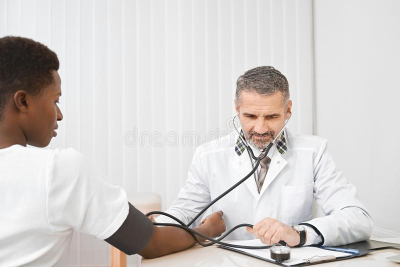 Patient in medical cabinet on measuring of blood pressure. Young african men sitting, holding hand on table, while doctor measuring blood pressure. Professional royalty free stock images