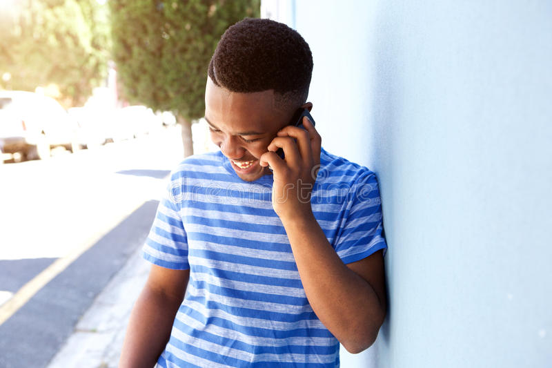 Young african man smiling and talking on mobile phone outside stock photo