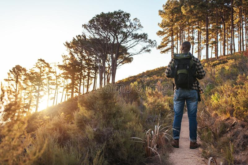 Young African man standing on a trail in the afternoon stock image